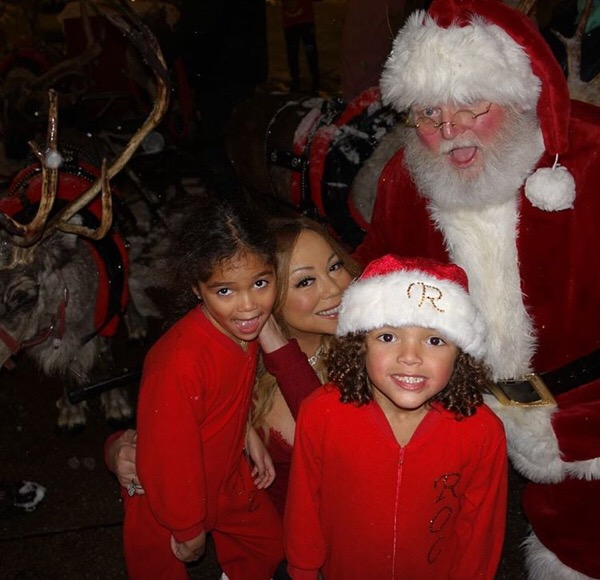 Mariah Carey and kids pose with Santa.