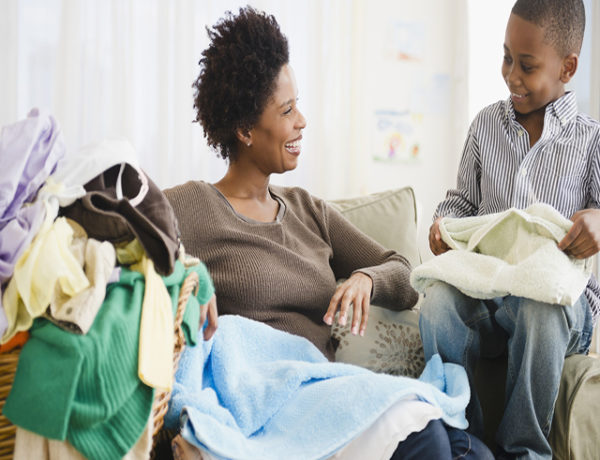 Black mother and son folding laundry