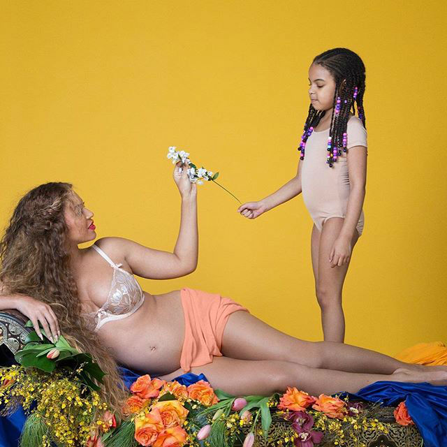 Blue Ivy hands the mom-to-be a flower.