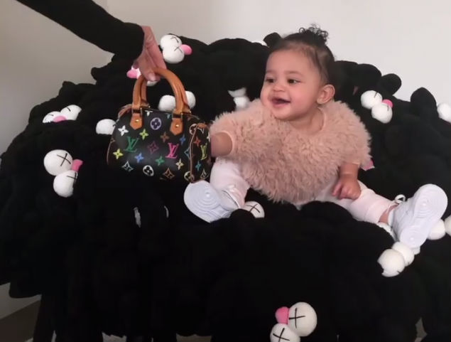 TRENDY TOT: STORMI WEBSTER SITS IN A PRICEY KAWS CHAIR WHILE HOLDING A MINI LOUIS VUITTON BAG