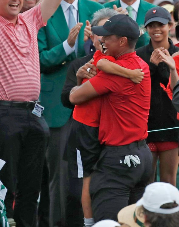 tiger woods celebrates with his children after masters win