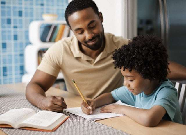 Father helping son (7-9) with homework --- Image by © Tim Pannell/Corbis